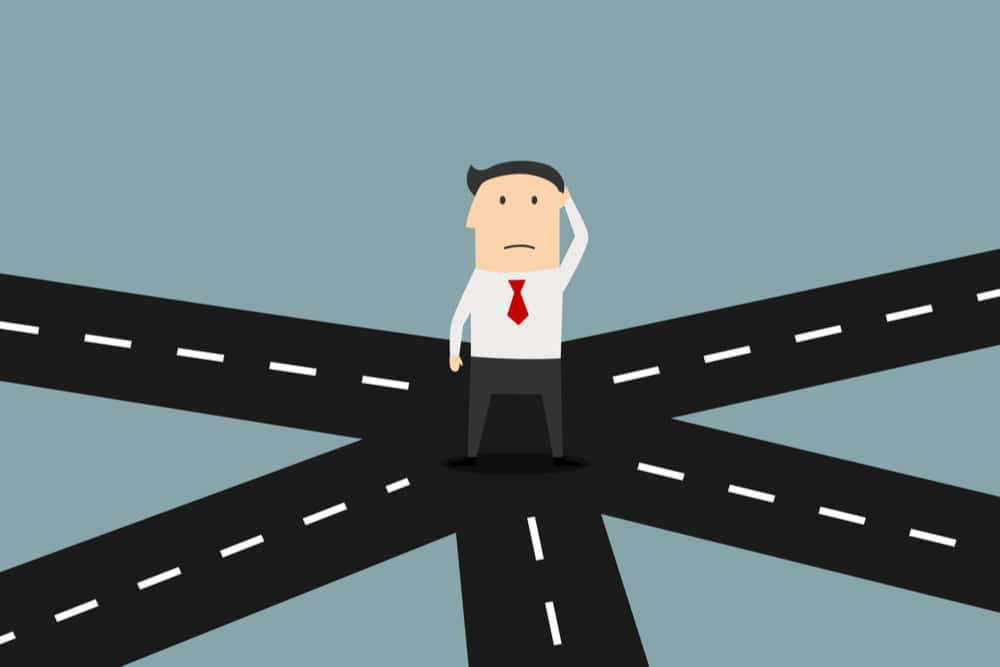 An animated business man standing in the middle of a crossroad thinking which way to go
